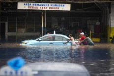 Residents move a car at the Blue Bird taxi pool in Kramat Jati, East Jakarta, on Jan. 1. Antara/Galih Pradipta