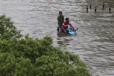 A motorcyclist rides through a flood on Jl. S. Parman in West Jakarta on Jan. 1. JP/Dhoni Setiawan