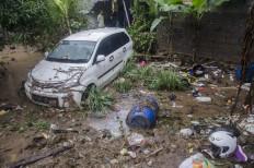 Residents stand near a damaged car after a flood in Cimareme, West Bandung, West Java, on Jan. 1. Antara/Novrian Arbi