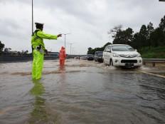 A traffic officer directs motorists at kilometer 8 of the Serpong toll road on Jan. 1, 2020. JP/R Berto Wedhatama