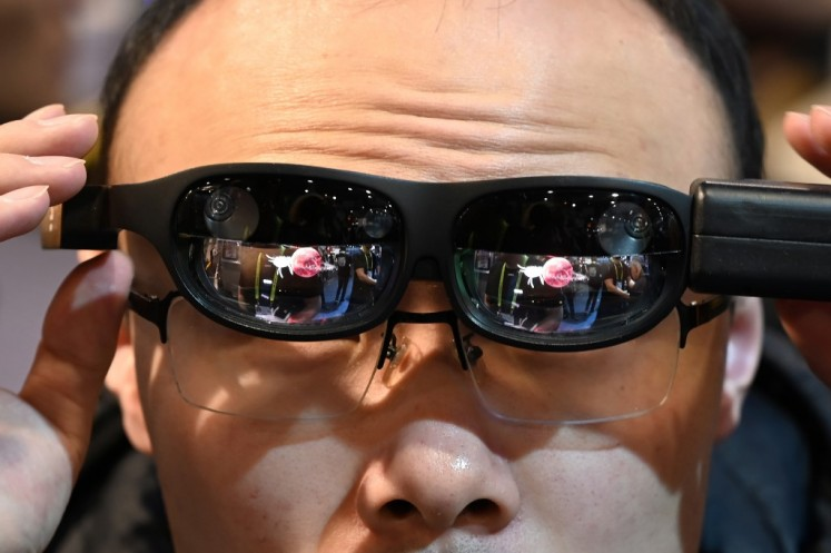 In this file photo taken on January 11, 2019, an attendee tries NReal augmented reality (AR) glasses, on the last day of CES 2019 at the Las Vegas Convention Center in Las Vegas, Nevada. The screens will be bigger and bolder, the cars will be smarter and some of the technology will be up-close and personal -- even intimate. The 2020 Consumer Electronics Show opening in Las Vegas will be crammed with the latest in connected devices, from light bulbs to underwear, along with the newest technology for automobiles, health and wellness, smart homes, retailing and more. One of the world's biggest trade shows, the gathering features 4,500 exhibitors, an estimated 175,000 attendees, and 1,000 speakers in exhibit areas equivalent to more than 50 football fields. The CES runs from January 7 to 10.