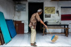 Rama Dwijo sweeps the outer area of the KHP Kridha Mardawa before the class starts. JP/Anggertimur Lanang Tinarbuko