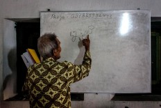 Rama Dwijo writes Javanese script on a whiteboard. JP/Anggertimur Lanang Tinarbuko