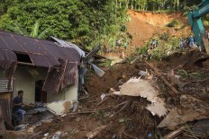 Recovery starts now: A rescuer searches through the wreckage of a building destroyed by flooding and a landslide in Sangihe, North Sulawesi, on Saturday. The flood hit on Friday and killed three residents while displacing more than 300 others. Antara/Stenly Pontolawokang