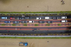 Get in line: Cars use an underpass as a flood inundates Jl. Angkasa in Central Jakarta on Thursday. Antara/Sigid Kurniawan