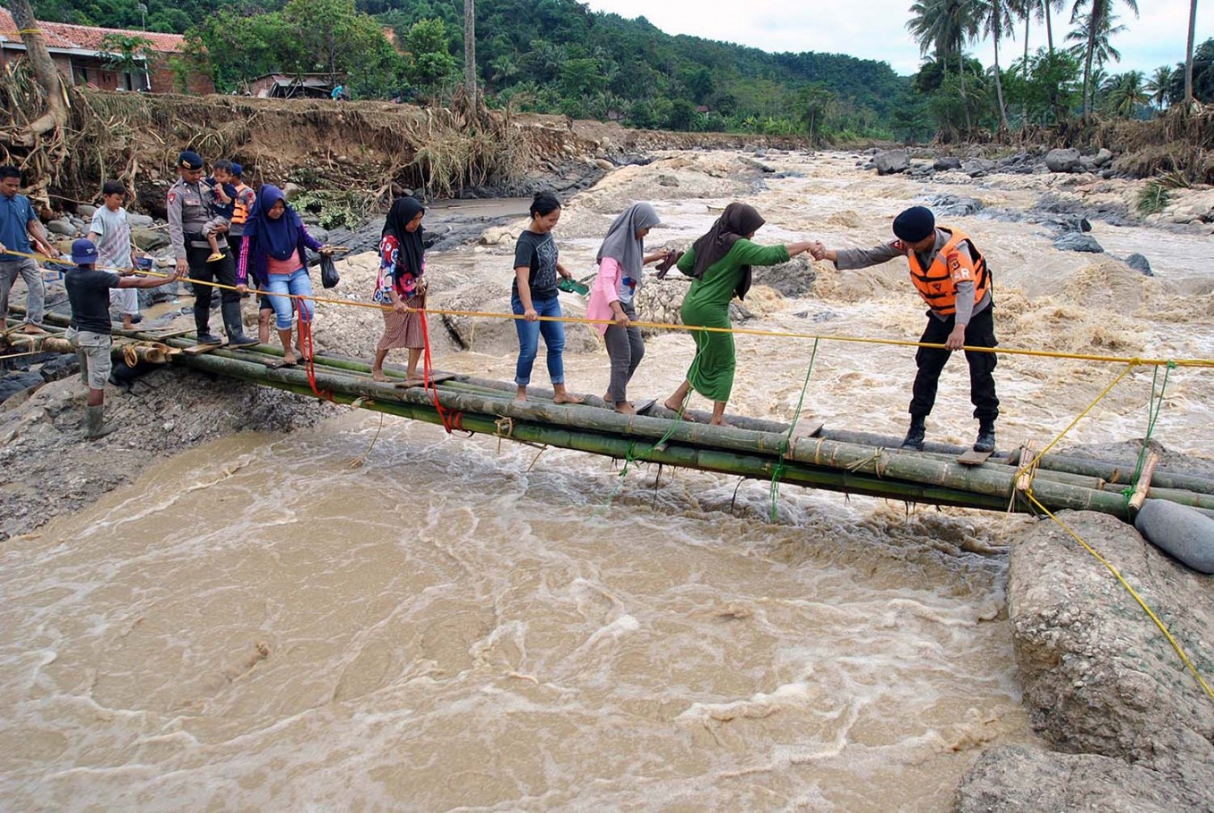 Work together: A police officer helps residents cross a makeshift emergency bridge over the Cidurian River in Bogor, West Java, 