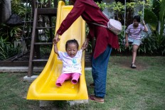 afitri Zaskia, 3, plays with her mother before her scheduled practice at Puspadi. Born in East Lombok, Safitri came to Bali to receive her first prosthetic legs with the help of the Lombok Disability Center and Endri's Foundation. JP/Agung Parameswara