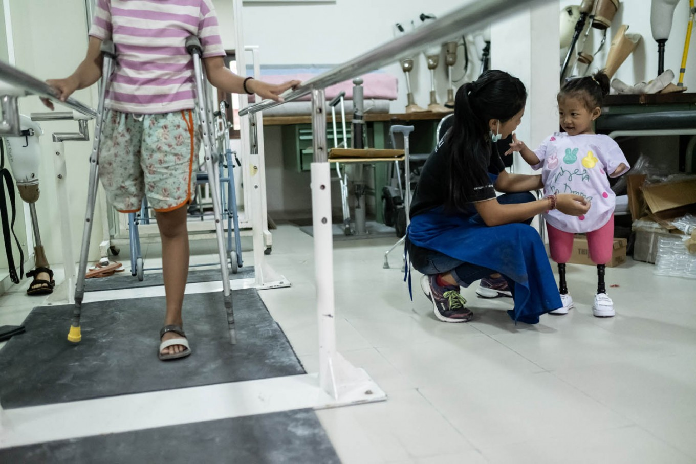 Putu chats with Safitri, while Ulil, 13, practices walking with the assistance of metal rails. Ulil lost her right leg as a toddler because of a malignant tumor. JP/Agung Parameswara