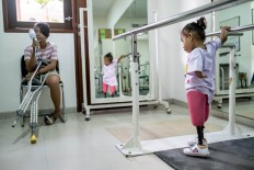 Safitri holds metal rails as she practices walking with her prosthetic legs. JP/Agung Parameswara