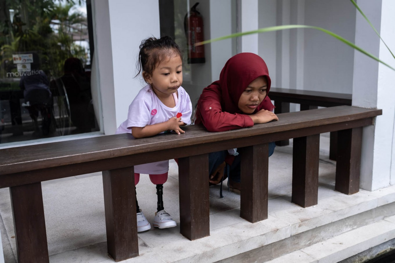 """Safitri and her mother Sofiani look at a fish pond. """"She is excited about going to school now that she's the same height as everybody else,"""" Sofiani said of her daughter's enthusiasm. JP/Agung Parameswara"""