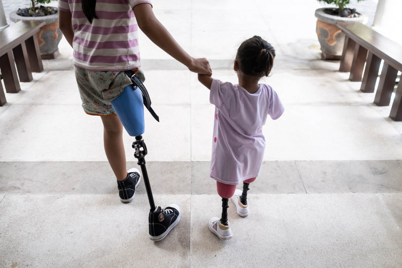 Ulil and Safitri walk hand in hand as they practice with their prosthetic legs they have long waited for. JP/Agung Parameswara