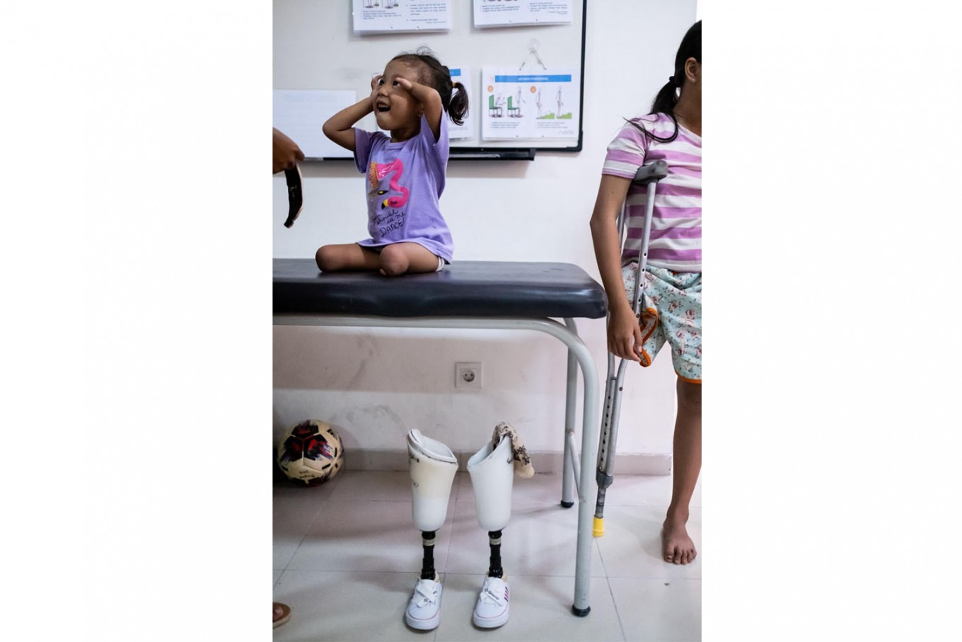Safitri smiles after practicing to walk with her prosthetic legs. JP/Agung Parameswara