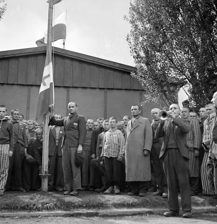 French prisoners raise the flag of Free France with the Lorraine cross while singing the national anthem, 'La Marseillaise', 29 April 1945 upon the liberation of the Nazi concentration camp of Dachau, near Munich, by Allied troops.