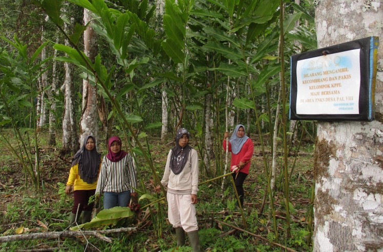 Members of farmers group Maju Bersama stand near a sign telling people to stay out of their cultivation area.
