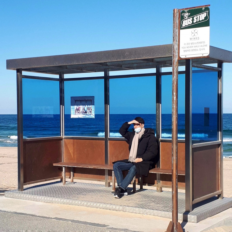 A man sits in a replica of a bus stop used for the shoot of BTS' music video
