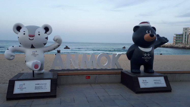 An Anmok Beach sign featuring mascots from the 2018 Winter Olympics in neighboring Pyeongchang county.