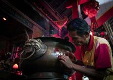A temple caretaker cleans an incense jar. JP/Bismo Agung