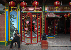 A resident who works as the temple's caretaker sits in front the Hok Lay Kiong temple on Jan. 24. JP/Bismo Agung
