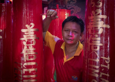 Pepen, who is not of Chinese descent, works at the temple and writes prayers on candles. He comes from Sukabumi, West Java, and has worked there for 20 years. JP/Bismo Agung