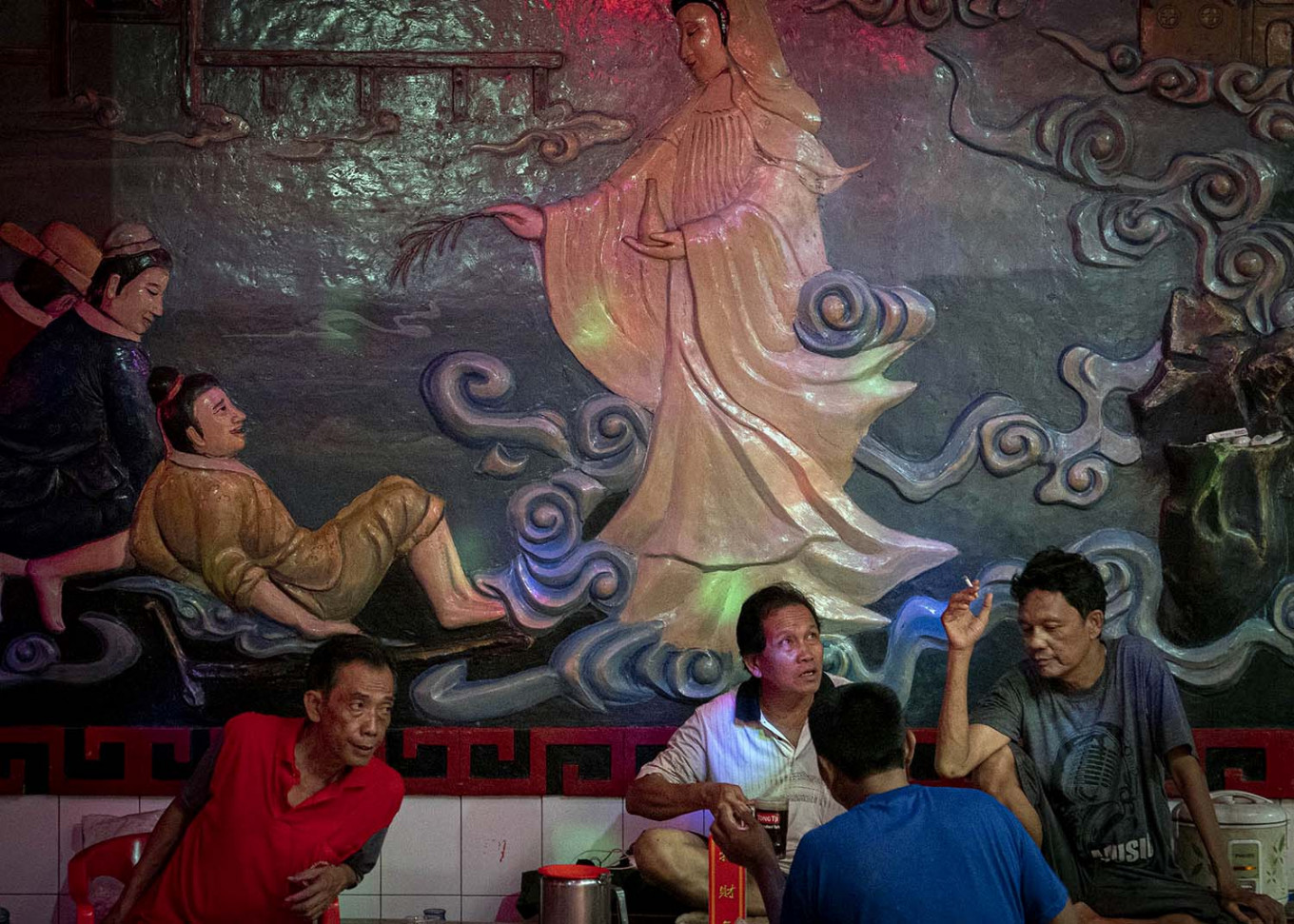 The temple's caretakers chat during a break from work. JP/Bismo Agung
