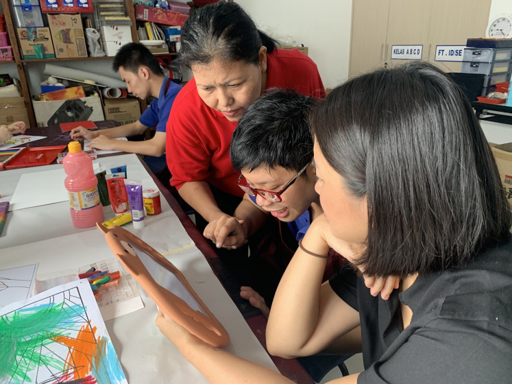 Sam (second right), 26, a Kyriakon workshop student, uses his iPad to communicate with teacher Ratmi (left), and a volunteer, Amanda, as he chose colors for his drawing.
