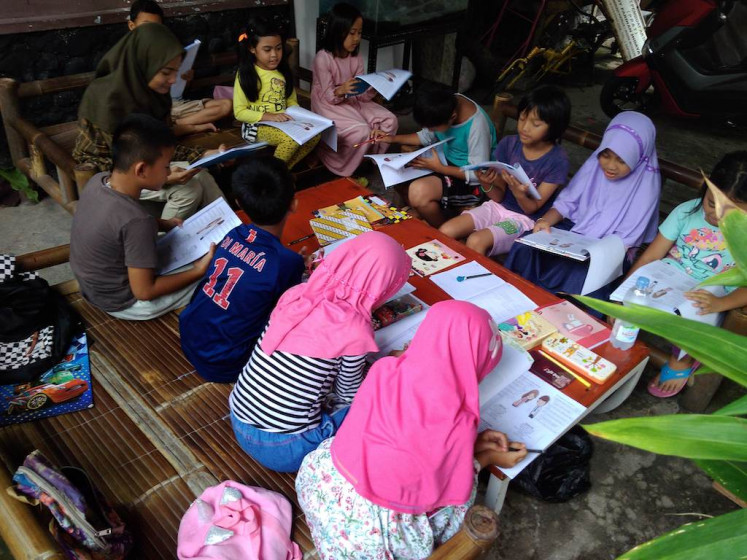 Children learn English with Irmanda Sri Amri, a student of Jakarta State University (UNJ) and volunteer at the Sempur English Camp in Bogor, West Java, on Jan. 21.