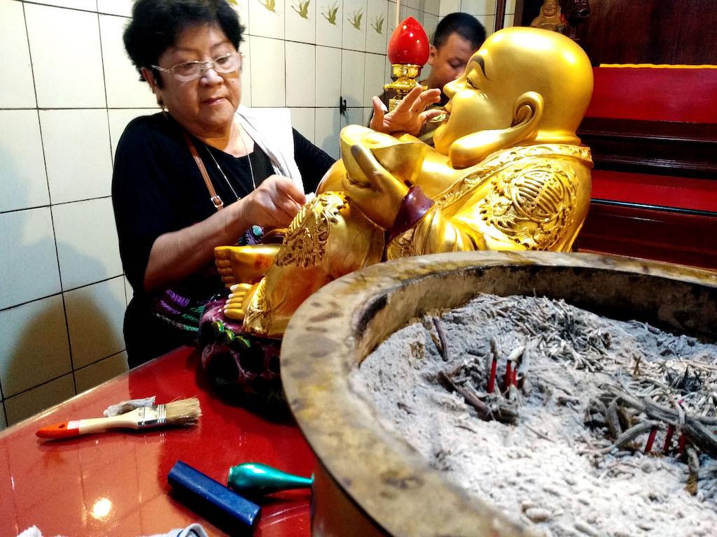 A Confucian cleans a statue of a god at Tjoe Hwie Kiong Temple.