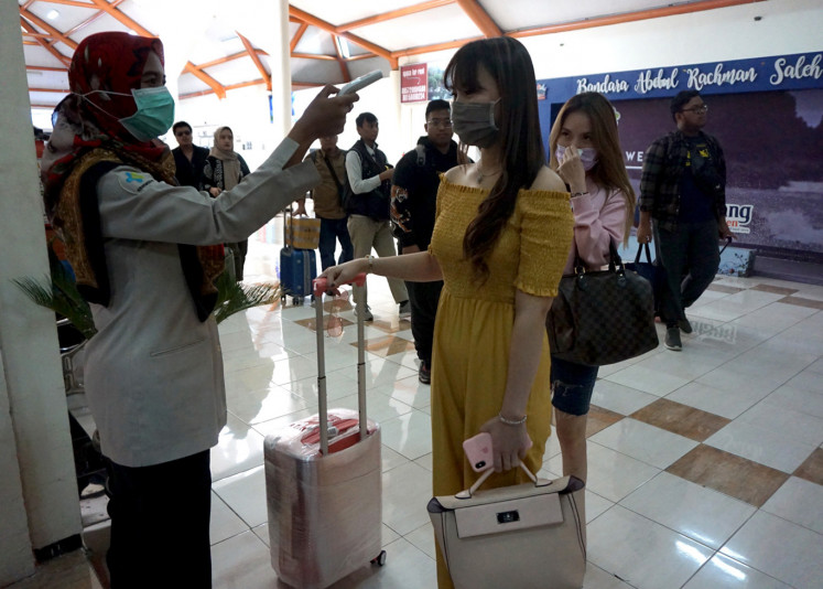 Health Ministry officials take the temperatures of newly arrived passengers at Abdulrachman Saleh Airport in Malang, East Java, on Jan. 27.