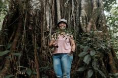 Volunteer Ditha holds two banyan plants. JP/Anggara Mahendra