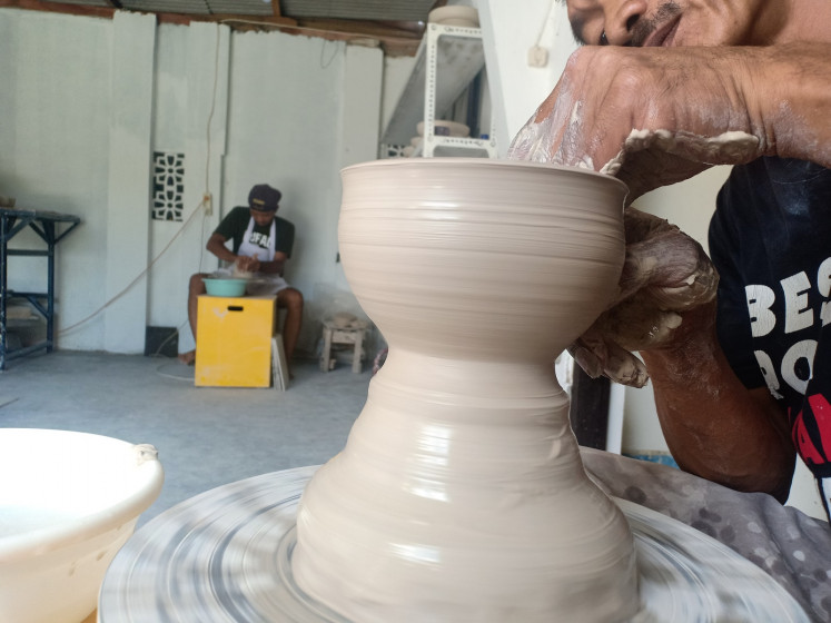 A Kaloka Pottery employee in the process of creating a product
