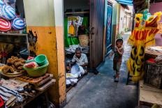 Curiosity: A passing boy watches the process of making barongsai equipment inside Doel's workshop. JP/Anggertimur Lanang Tinarbuko