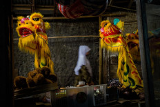 Finished products: A woman passes between two barongsai lion heads hung by Doel in front of his workshop. JP/Anggertimur Lanang Tinarbuko