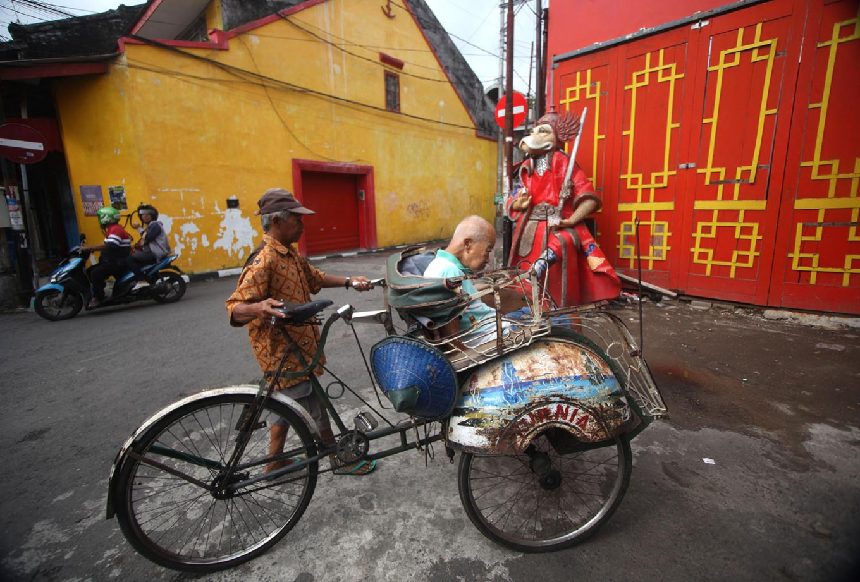 A becak (pedicab) driver takes a customer through Kampung Ketandan. JP/Boy T Harjanto