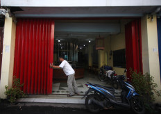 A man opens the door to a gold shop. JP/Boy T Harjanto