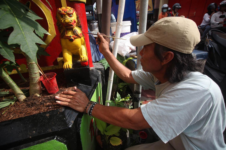 A man repaints a statue in Kampung Ketandan. JP/Boy T Harjanto