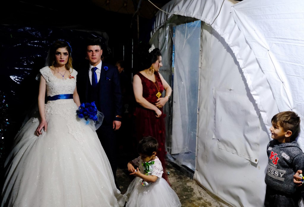 Sundus Garis (left), 16, and Farid Mallo, 19, both from the beleaguered Yazidi community who were displaced from northern Iraq's Sinjar region, are pictured outside a tent before leaving the Kabarto 2 camp for internally displaced people to the wedding hall in the nearby northernwestern Iraqi Kurdish city of Dohuk, not far from the border with Turkey, on January 23, 2020.
