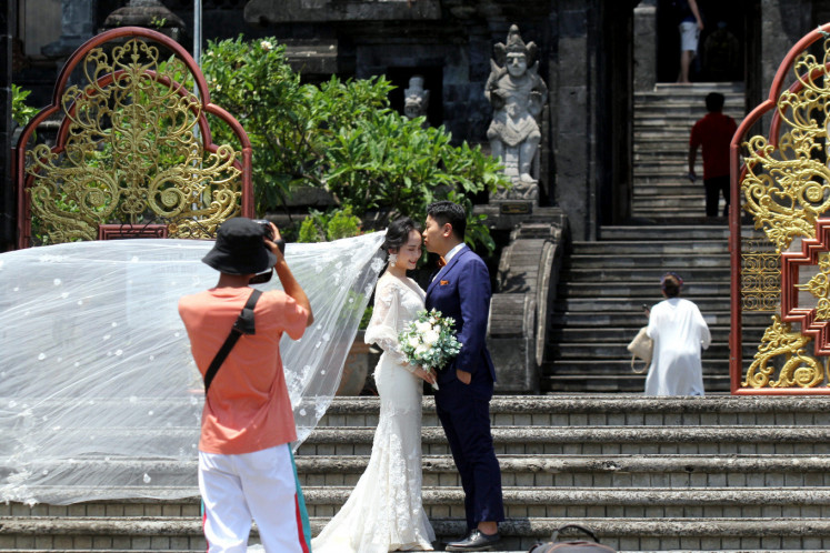 Two Chinese tourists take a shoot during a prewedding in Bajra Sandi monument tour, Denpasar, Bali, on Wednesday, January 29. 2020.