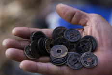 Blast from the past: Antique coins are held up by a treasure hunter. They are believed to have belonged to Chinese merchants and to have originated in Holland. JP/ Sigit Pamungkas
