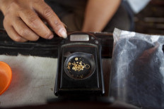 Gram by gram: A trader weighs gold fragments found by a treasure hunter. JP/ Sigit Pamungkas