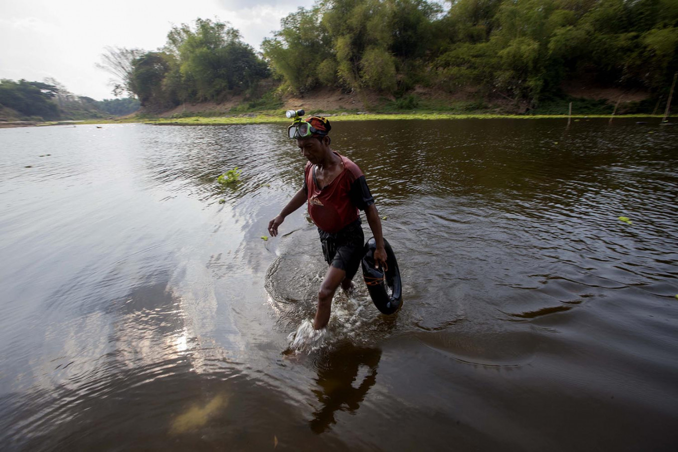 Another day: A treasure hunter walks to the riverbank after searching for valuables in its depths. JP/ Sigit Pamungkas