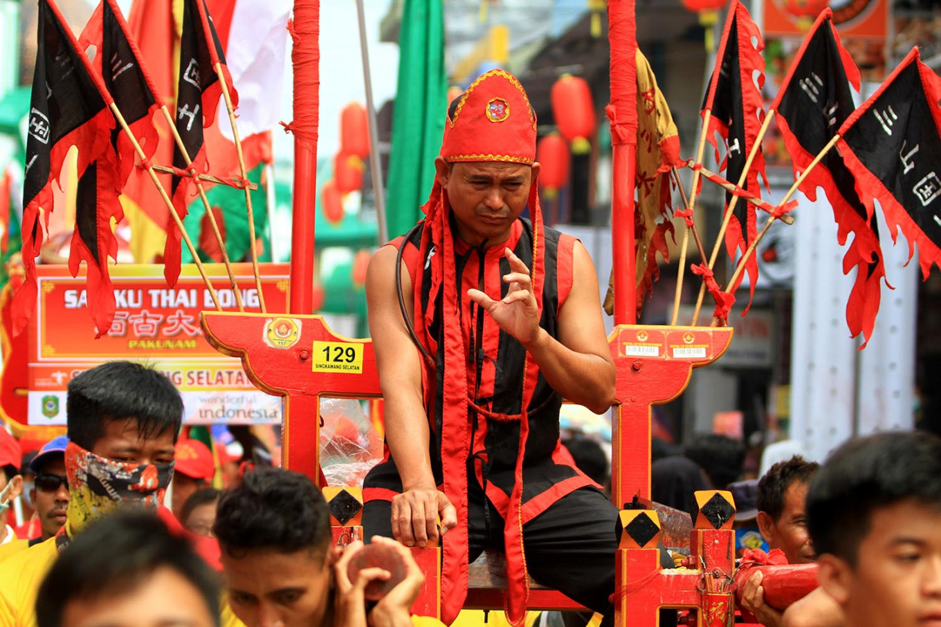 A tatung shows off his ability of sitting on a machete during the parade. JP/HS Putra