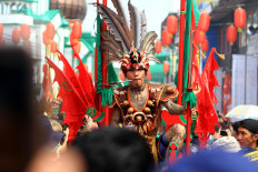 A tatung, in Dayak-inspired costume, has a thick metal stick stabbed through his cheek. JP/HS Putra