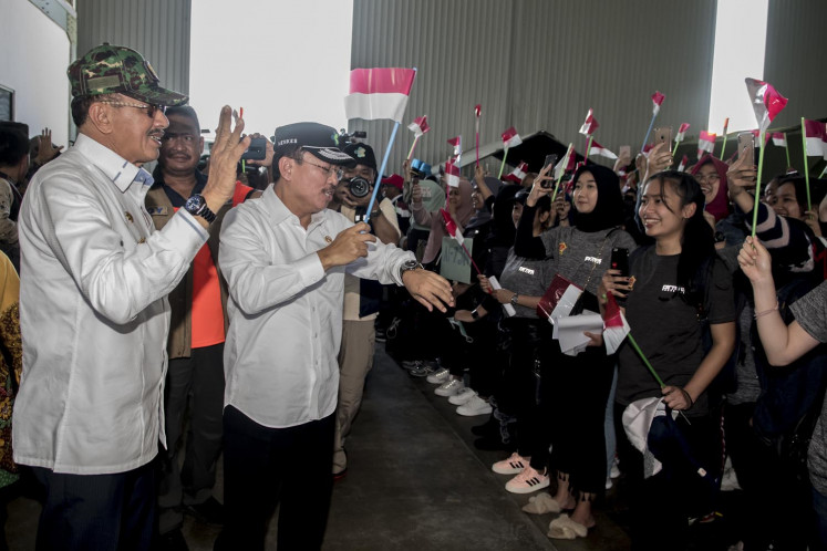 Health Minister Terawan Agus Putranto (second left) congratulates the crowd of people newly released from quarantine on Feb. 15, 2020 at Raden Sadjad Air Base in Natuna, Riau Islands. All evacuees, the evacuation team and support staff were declared free of coronavirus infection and departed the island on Saturday, where they had been quarantined since Feb. 2.