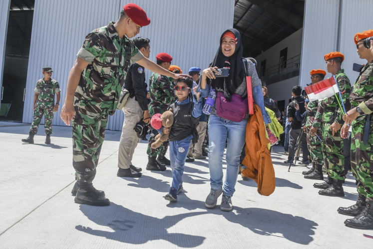 A soldier of the Joint Defense Area Command I (Kogabwilhan I) pats a child on the head on Feb. 15, 2020 at Raden Sadjad Airbase in Natuna, Riau Islands. All evacuees from Wuhan, China, were given a clear bill of health and left the air base  hangar where they had been quarantined since Feb. 2.