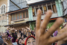 Hands up: Residents hold up their hands before trying to catch sachets of sugar in front of the Muhammadan Mosque in Padang, West Sumatra.  JP/Ramadhani
