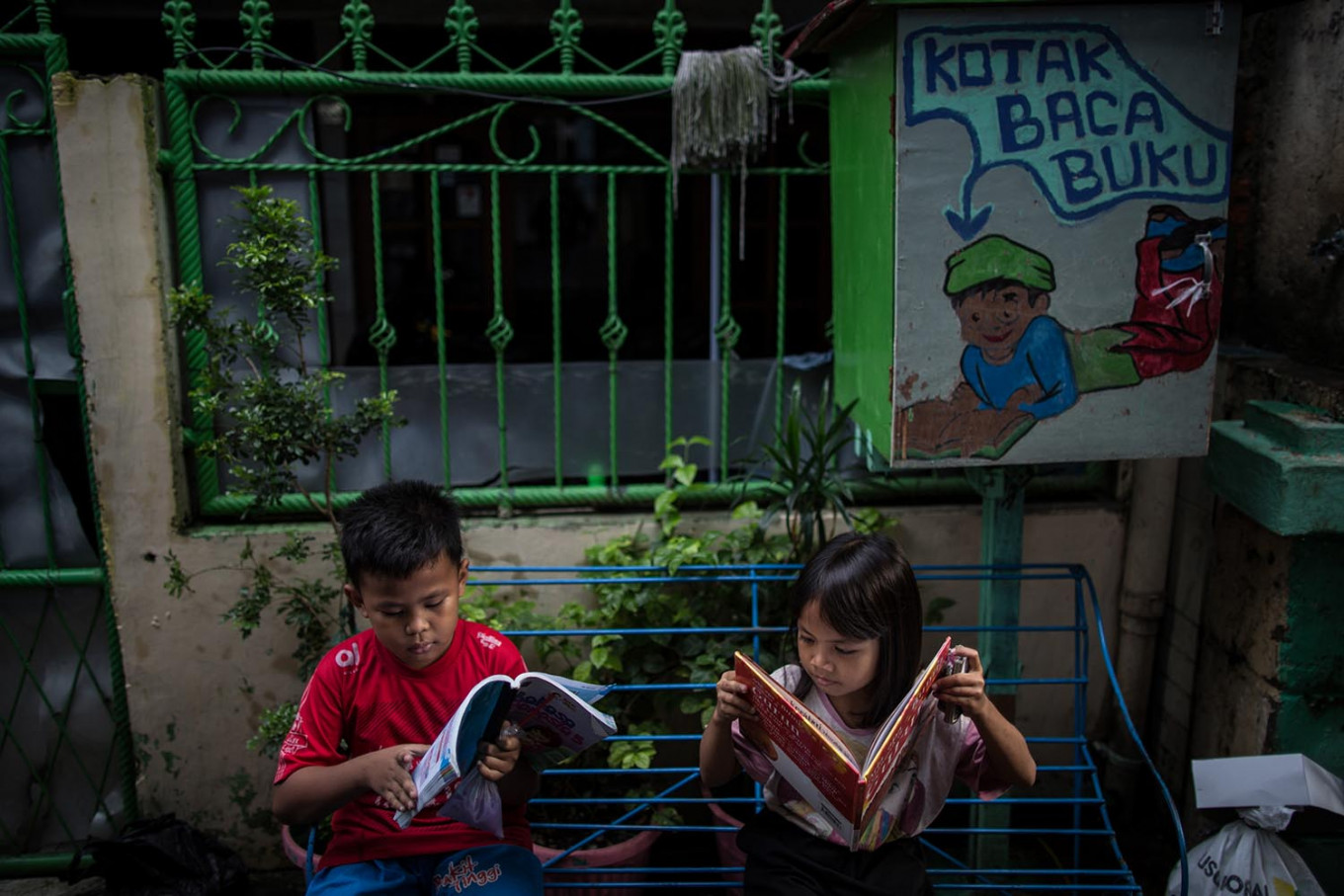 Two children of the Jatipulo literacy kampung read books, seated on a bench beneath a decorated book-sharing box. JP/Afriadi Hikmal