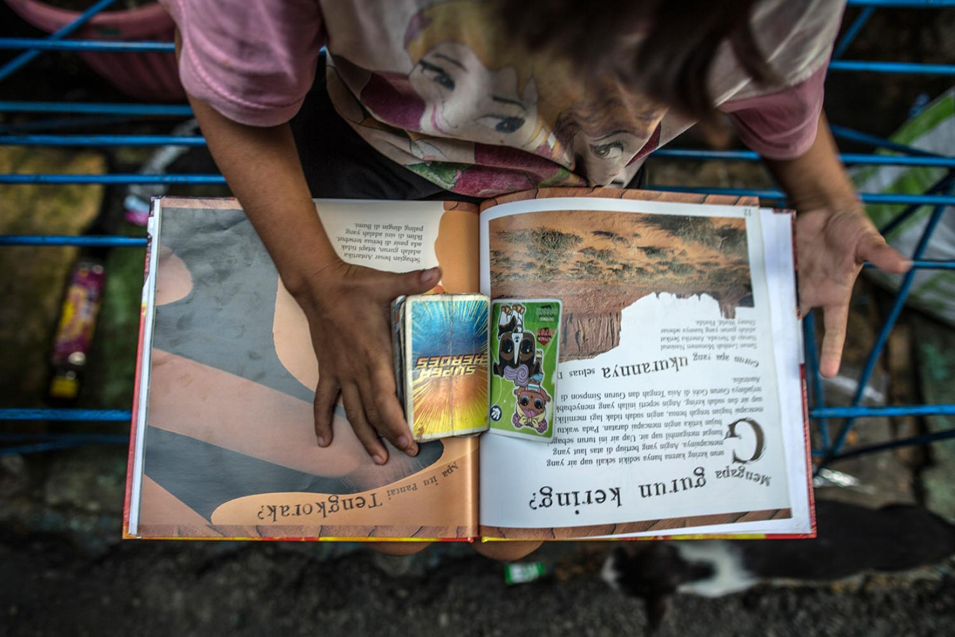 Aini flips through superhero character cards amid pages on desert geography in the Jatipulo literacy kampung. JP/Afriadi Hikmal