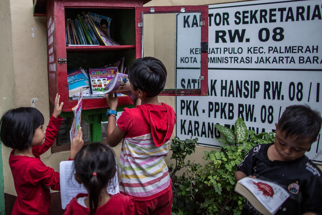 Children browse through books from a book-sharing box in Jatipulo subdistrict, West Jakarta. The books have all been donated to the community in its initiative to turn the neighborhood into a literacy kampung. JP/Afriadi Hikmal
