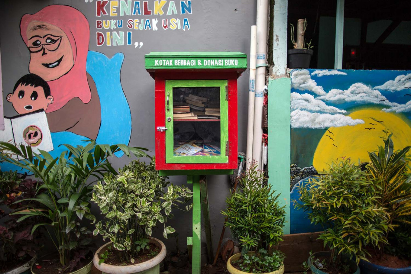 A colorfully painted book-sharing box offers free reading material along an alley in Jatipulo subdistrict, West Jakarta. JP/Afriadi Hikmal
