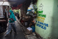 """A woman walks past Gang Z on Feb. 4, 2020, where a painted sign welcomes people to the """"kampung literasi"""" in Jatipulo subdistrict, West Jakarta. JP/Afriadi Hikmal"""